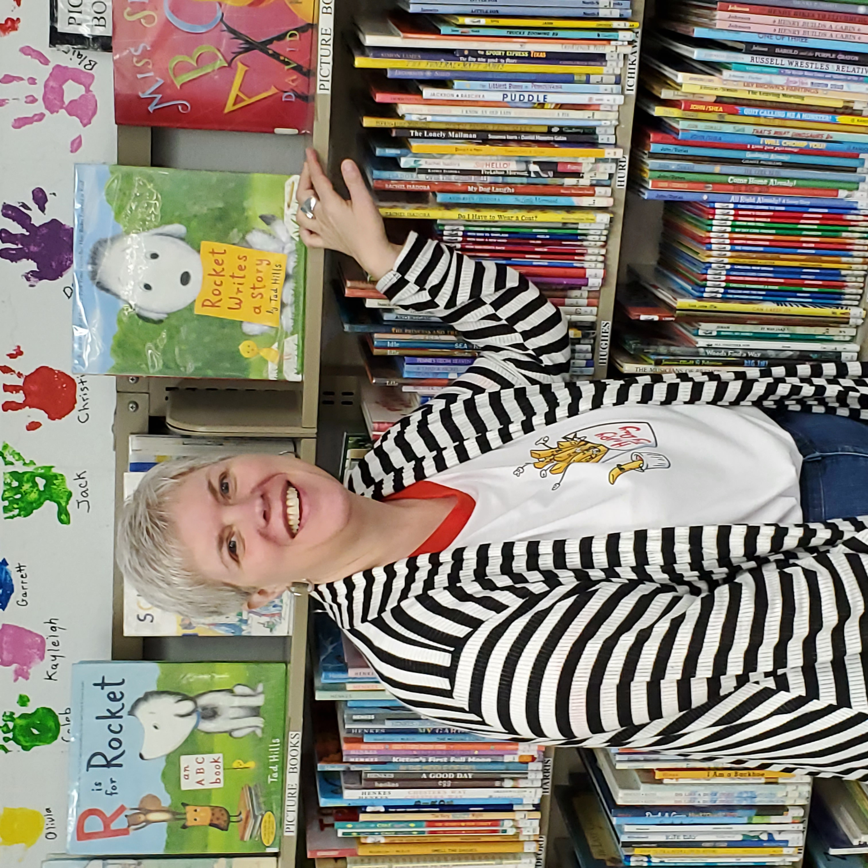 Jennifer Johnson-Spence standing in front of a shelf of children's books in her library.